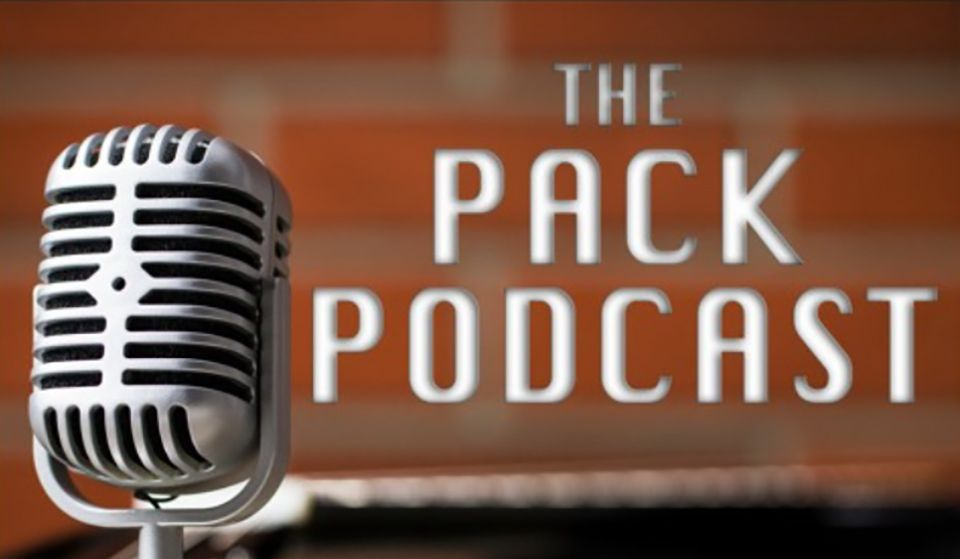 """Close-up of a microphone in front of a brick wall. To the right, the words """"the Pack Podcast"""""""